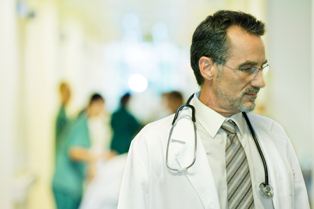 Male doctor looking away, head and shoulders, hospital corridor in background LANG_EVOIMAGES