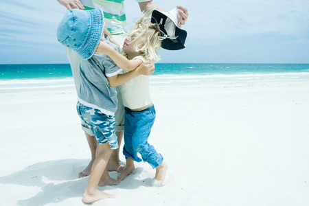 Family on beach, boy and girl reaching for each other in front of father LANG_EVOIMAGES