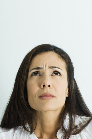 puzzlement: Woman furrowing brow, looking up, portrait