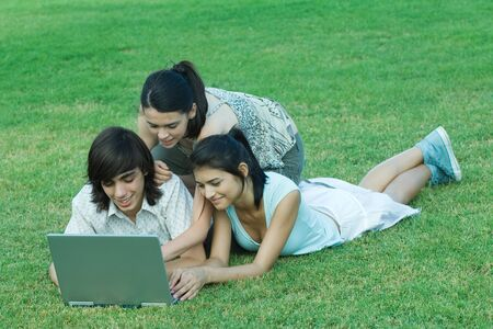 Young friends lying in grass, using laptop together