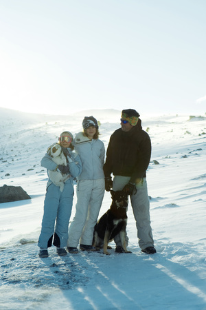 Man and two daughters standing in snow with two dogs, full length portrait