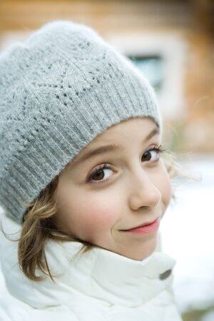 Girl in winter clothes smiling at camera, close-up