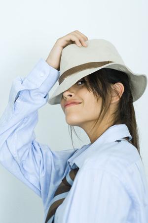 vistiendose: Muchacha adolescente con camisa, corbata y sombrero, mirando a cámara LANG_EVOIMAGES