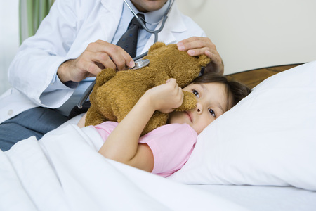 Doctor holding stethoscope to sick childs teddy bear