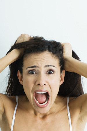 Woman pulling hair and screaming at camera, portrait