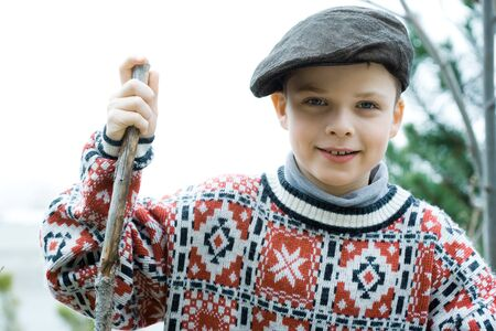berets: Boy wearing traditional sweater and cap, holding hiking stick