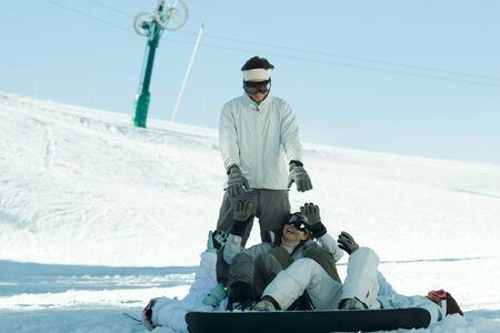 kids at the ski lift: Young snowboarders lying on ground reaching for young man standing behind them LANG_EVOIMAGES