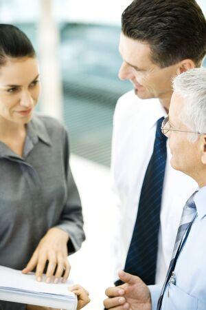Business associates standing together, one holding file LANG_EVOIMAGES