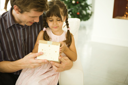 Father and daughter opening present together, Christmas tree in background