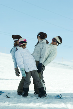 Group having fun in snow, full length