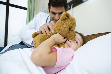 Doctor holding teddy bear up to sick childs face
