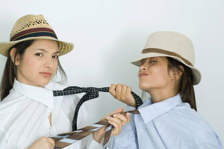 Two young female friends dressed in hats, pulling each others ties, one frowning, the other smirking LANG_EVOIMAGES