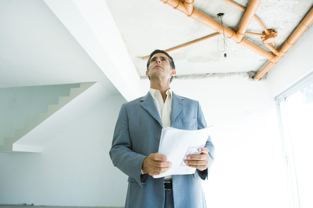 Well-dressed man holding blueprints, inspecting unfinished home interior
