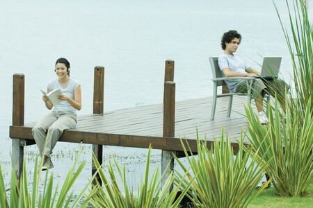 percepción: Young man and woman sitting apart on dock, woman reading book, man using laptop