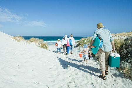 over the edge: Family walking through dunes to beach