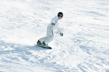 Teenage girl snowboarding down ski slope, full length LANG_EVOIMAGES