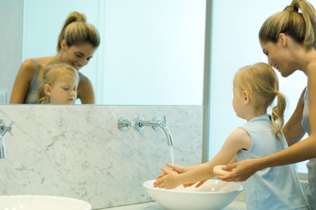 oneself: Woman helping little girl wash hands in bathroom sink