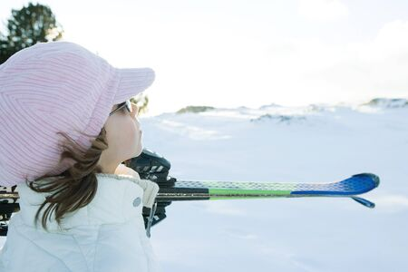 Girl carrying skis on shoulder, looking away, side view LANG_EVOIMAGES