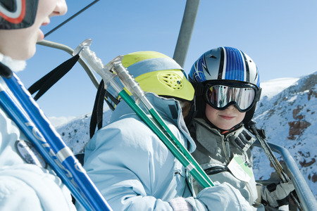 kids at the ski lift: Young skiers on chair lift, one whispering in the others ear