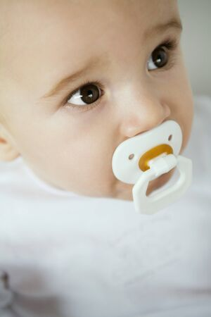 Baby with pacifier in mouth, close-up