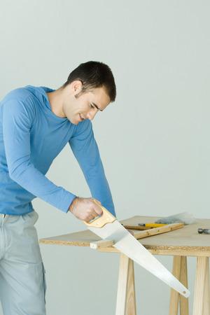 Man sawing wood plank LANG_EVOIMAGES