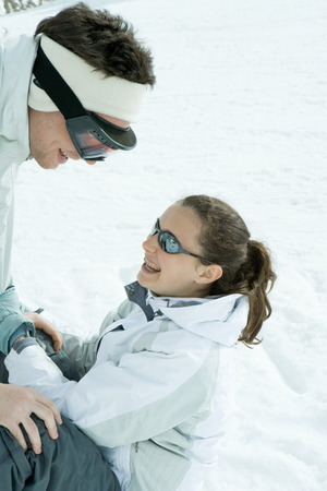 Brother and sister face to face in snow, brother bending over, sister sitting on the ground LANG_EVOIMAGES