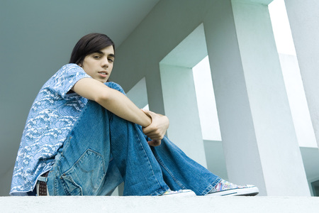 Teen boy sitting with knees up