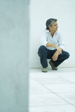 Mature man crouching, looking away, smiling, full length portrait