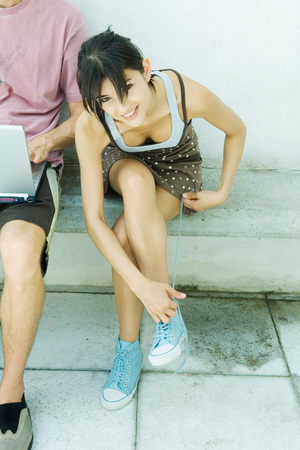 Young woman tying laces, smiling at camera
