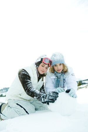 Two teenage girls crouching in snow, building snowball together, one smiling at camera