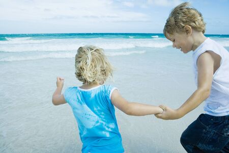 Children holding hands on beach