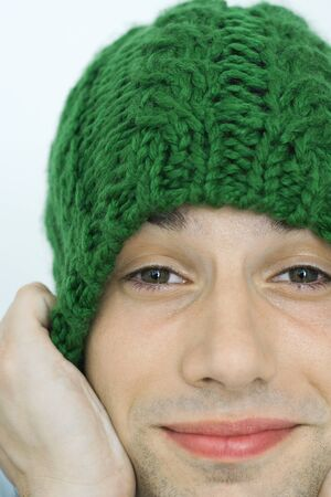 embarrassment: Young man pulling down knit hat over ears, portrait, close-up