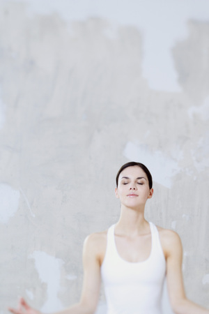 Woman sitting in lotus position, eyes closed, waist up LANG_EVOIMAGES