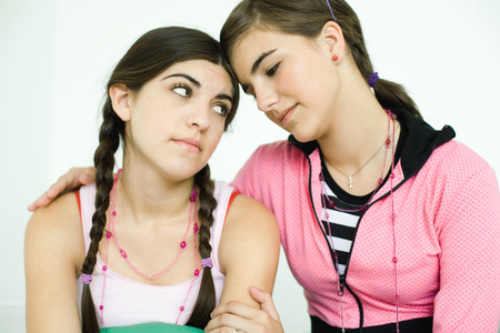 Two young female friends, one comforting the other LANG_EVOIMAGES