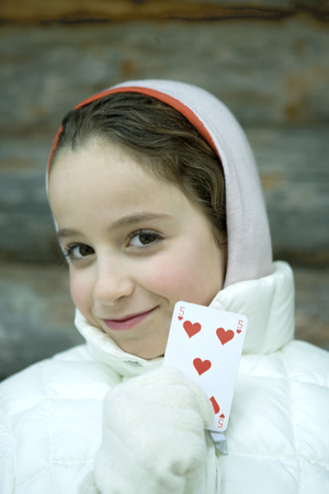 Girl in winter clothes holding up playing card LANG_EVOIMAGES