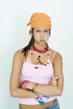 Teen girl wearing lots of accessories, arms folded, blowing cheeks out, portrait LANG_EVOIMAGES