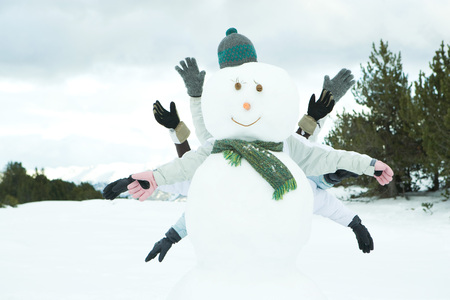 Young friends hiding behind snowman, arms out LANG_EVOIMAGES