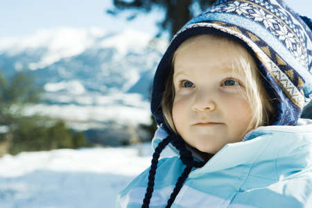 Toddler girl wearing winter clothes in snowy landscape, portrait LANG_EVOIMAGES