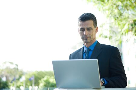 Businessman sitting outdoors, using laptop computer