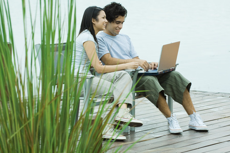 Young couple sitting on dock together, using laptop