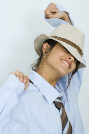 Teenage girl wearing tie and hat, smiling at camera, arms raised, portrait