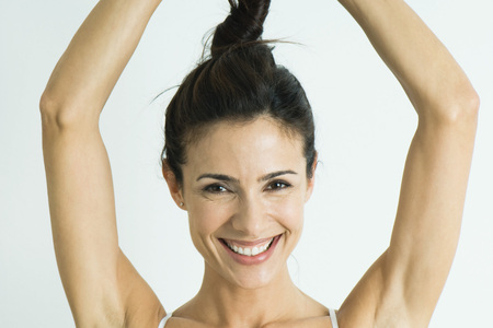 Woman twisting hair up above head, smiling at camera, portrait