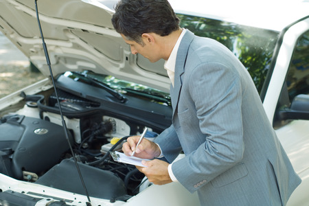 Mature man in suit inspecting car