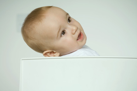 grey eyed: Baby sitting in chair, leaning head back