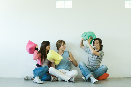 Group of young friends having pillow fight
