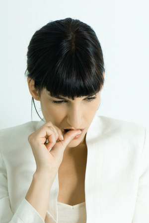 Well-dressed young businesswoman biting thumb, portrait