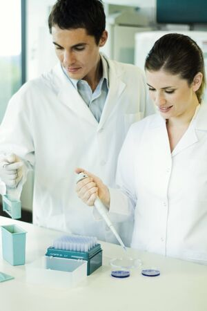 Female lab worker dropping solution into Petri dish, standing next to male colleague