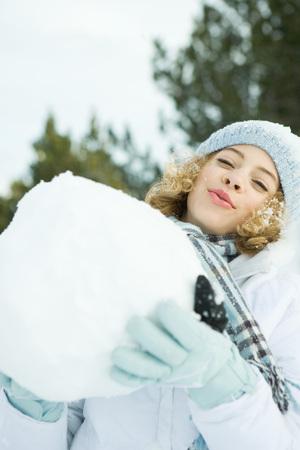 Teenage girl holding up large snowball, smiling at camera, head back