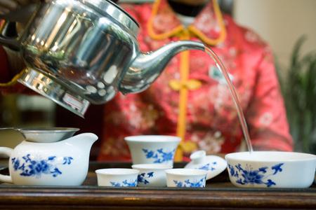 Woman serving tea, cropped view