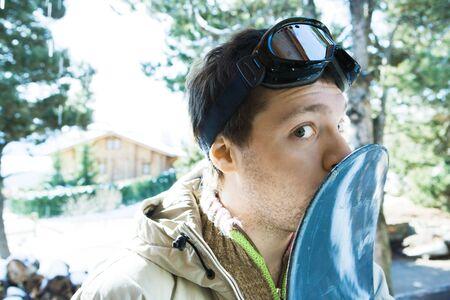 smooching: Young man kissing snowboard, glancing at camera